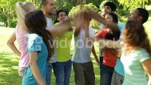 Group of casual young friends putting their hands together