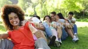Group of casual young friends sitting in a row messing