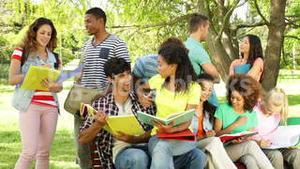 Happy students reading and chatting together outside on campus
