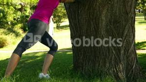 Woman stretching against a tree