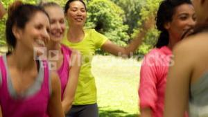 Smiling zumba class dancing in the park