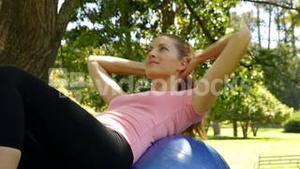 Fit woman doing sit ups on exercise ball in the park