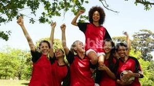 Female football team celebrating a win in the park