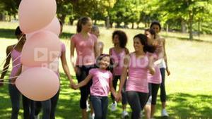 Happy women going on a walk for breast cancer awareness in the park