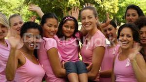 Happy women in pink for breast cancer awareness in the park waving at camera