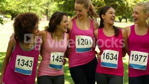Happy woman racing pink for breast cancer awareness in the park