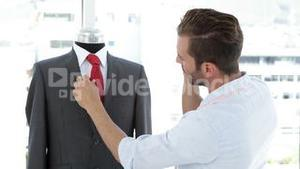 Handsome tailor touching suit and talking on phone