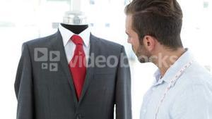 Handsome tailor using tablet beside suit on mannequin