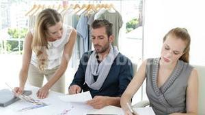 Fashion design team working together at table
