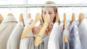 Attractive fashion designer looking at clothes on rail