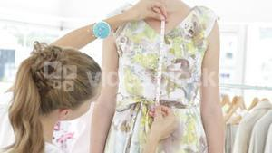 Pretty fashion designer measuring dress on a model