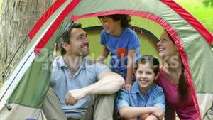 Family posing in their tent on a camping trip