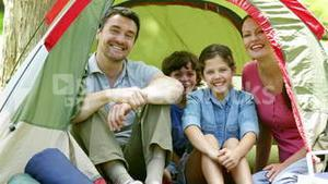 Happy family posing in their tent on a camping trip