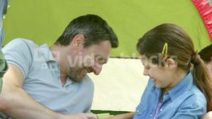 Happy family having fun in their tent on a camping trip
