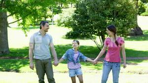 Happy parents and daughter jumping in the park
