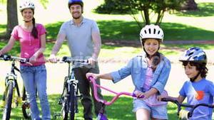 Smiling family on a bike ride in the park together