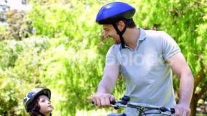 Father and young son on a bike ride in the park together