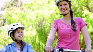 Happy mother and daughter on a bike ride in the park together