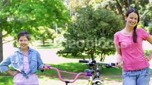 Cheerful mother and daughter on a bike ride in the park together