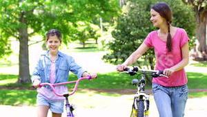 Cute mother and daughter on a bike ride together in the park