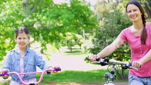 Cute mother and daughter pushing their bikes together in the park