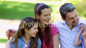 Cute family chatting together in the park