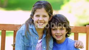Brother and sister embracing on park bench