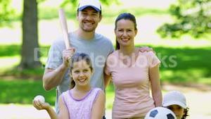 Sporty family smiling at camera in the park