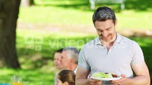 Happy father offering plate of food to camera at family barbecue