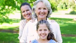 Three generations of women smiling at camera in the park