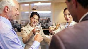 Business partners celebrating after work and drinking wine
