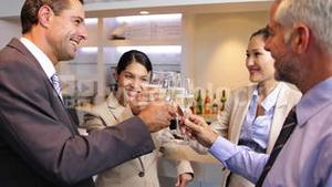 Business associates celebrating after work and drinking wine