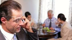 Businessman talking on phone at business lunch