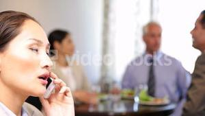 Businesswoman talking on phone at business lunch