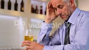 Worried businessman drinking a beer after work