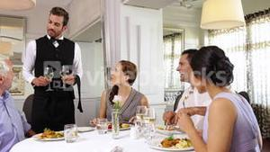Waiter attending to a table of friends