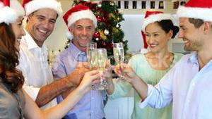Happy friends celebrating christmas together with champagne