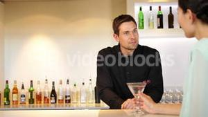 Bartender serving a cocktail and chatting to customer