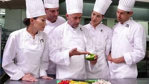Team of chefs watching head chef slicing vegetables
