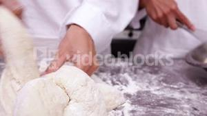 Pastry chefs preparing dough at counter