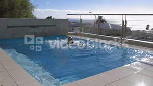 Woman jumping into pool fully clothed