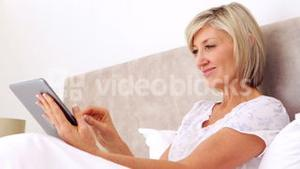 Happy woman using tablet in bed