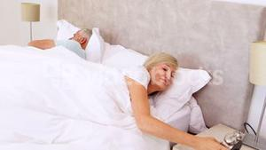 Peaceful couple sleeping in bed with woman turning off alarm