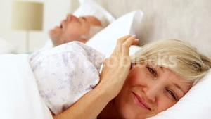 Woman covering her ears as partner is snoring loudly