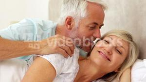 Couple relaxing in bed and smiling at camera