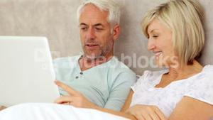 Happy couple chatting and using laptop in bed