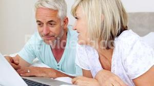 Happy couple lying on bed using laptop together