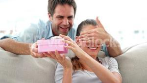 Man surprising his girlfriend with a pink gift on the sofa