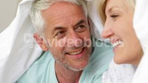 Smiling couple under the cover together in bed
