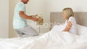 Romantic husband bringing his wife breakfast in bed